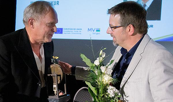 Festivalleiter Volker Kufahl  (rechts) gratuliert Ulrich Tukur (C) Jörn Manzke/FILMLAND MV